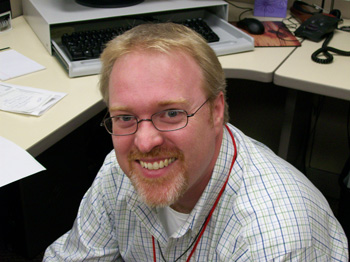 Photo of Clark posing at his desk