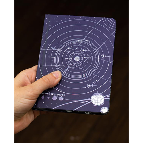 image of Solar System Mini Hardcover Dot Grid Journal in hand for scale