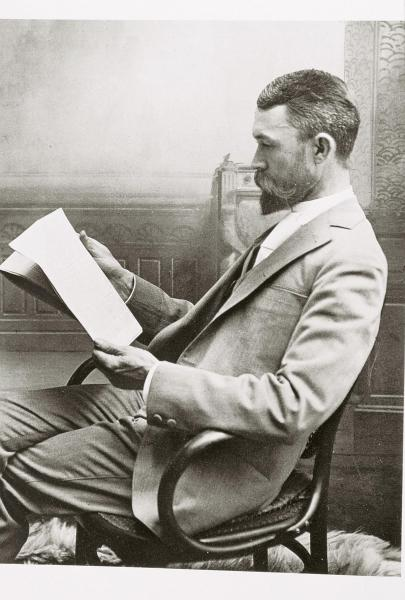 Black and white photo of Adam Clark Vroman reading in a chair