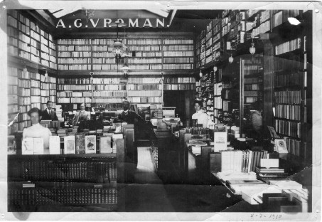 Black and white photo of the inside of the old store front, wall to wall shelves filled with books