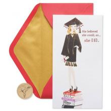 Image of girl in graduation cap and gown standing on a stack of books