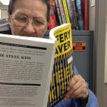 "Photo of Lee reading a copy of ""The Steel Kiss"""